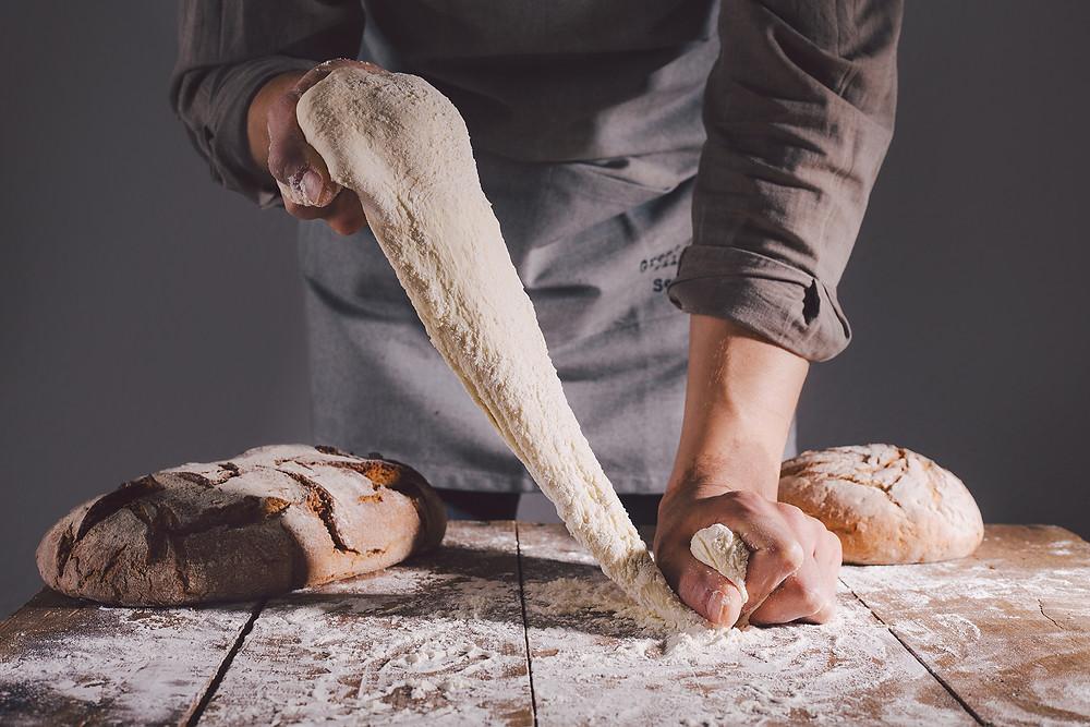 chef kneading dough bread