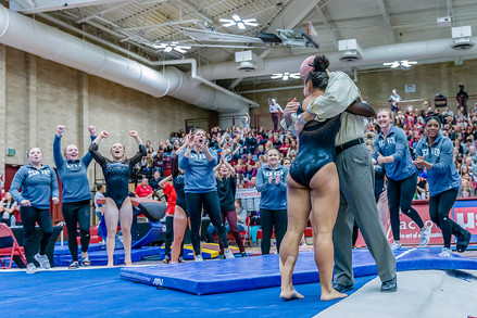 Nikole Addison celebrates with Coach Jay Hogue after floor exercise and scores 9.925, tied for 1st place.