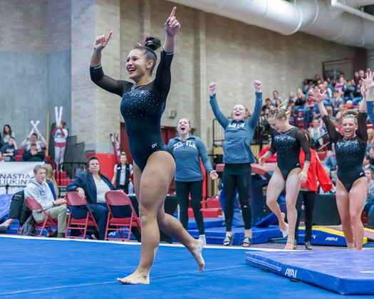 Nikole Addison celebrates after floor exercise and scores 9.925, tied for 1st place.