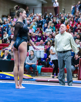 Kaitlyn Schou performing on the floor exercise with Jay Hogue looking on.