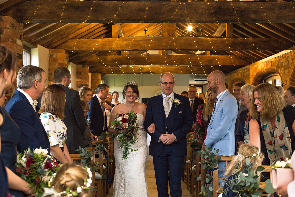 Bride walking down the aisle during wedding ceremony at Dodmoor House