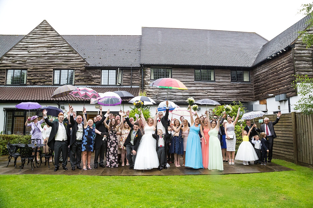Rainy group photo at Sketchley Grange Hotel wedding