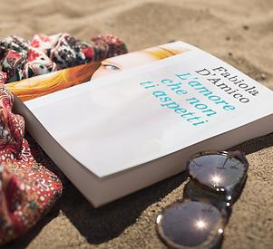 book-lying-on-the-beach-near-sunglasses-