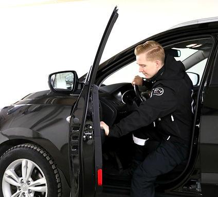 En mannlig sikkerhetsvakt som går inn i bilen sin