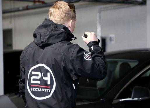 En sikkerhetsvakt som patruljerer i en garasje peker lommelykten mot en bil