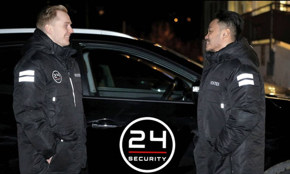 To mannlige sikkerhetsvakter som snakker foran en bil med 24 Securitys logotype