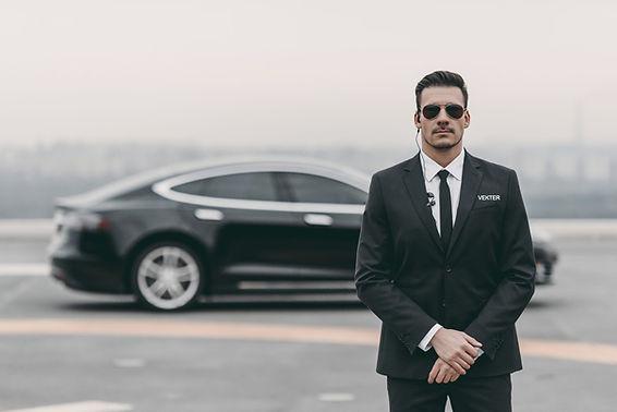 En personlig livvakt som poserer foran en Tesla Model X