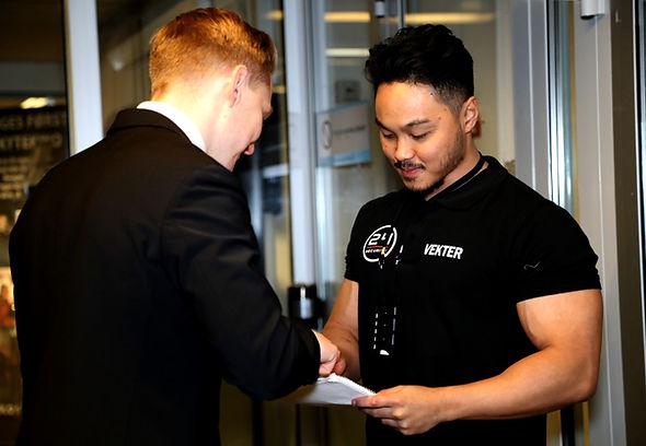 En sikkerhetsvakt sjekker navn fra en hendelses gjesteliste