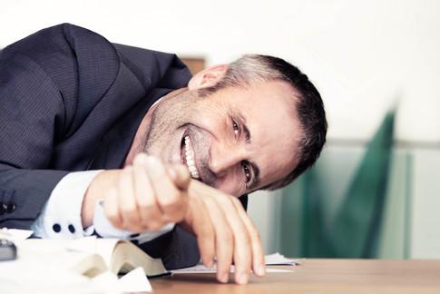 Geschaeftsmann-Schreibtisch-lachend.jpg
