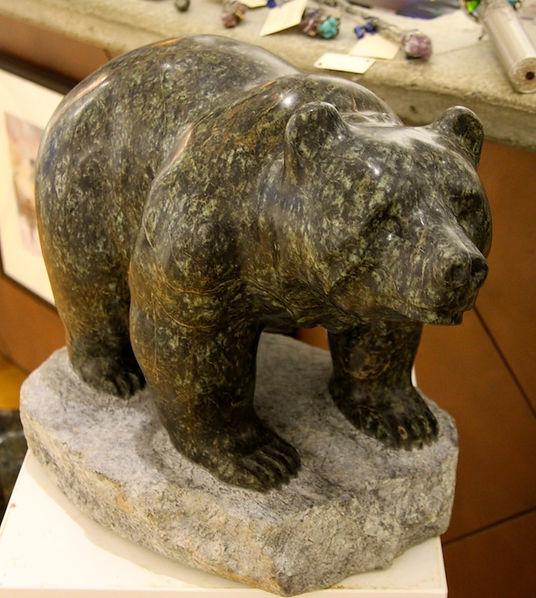 serpentine stone sculpture titled SOLD-Walking Bear-1 by sculptor cathryn jenkins.