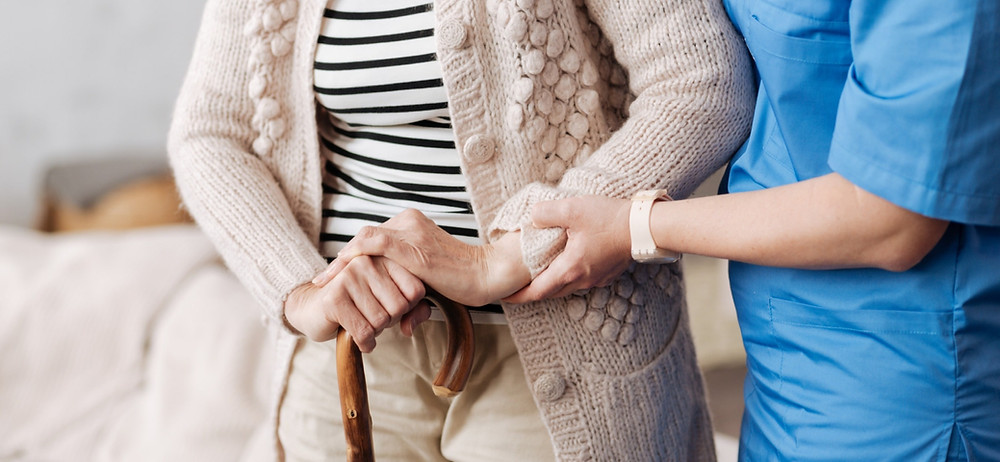 Nurse helping patient with walking stick