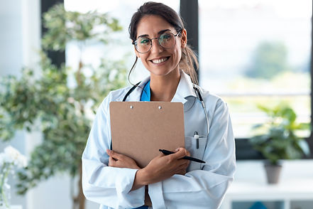 Beautiful female doctor looking at camera and smiling while holding medical documents and