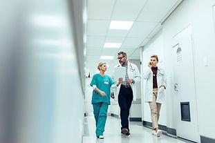 Group of medics discussing along hospital corridor-min.jpg
