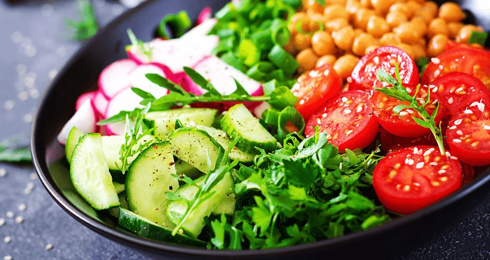 salad with chickpeas, arugula, tomatoes, an cucumbers.