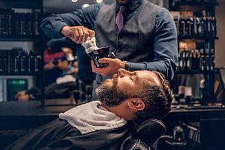 Barber applies shaving foam to a man's f
