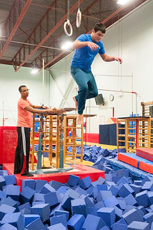 Adaptive athlete jumping into the foam pit