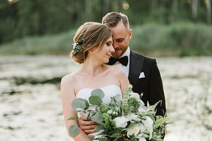 państwo młodzi przytulają się na tle jeziora w Weranda Home w Sławicy