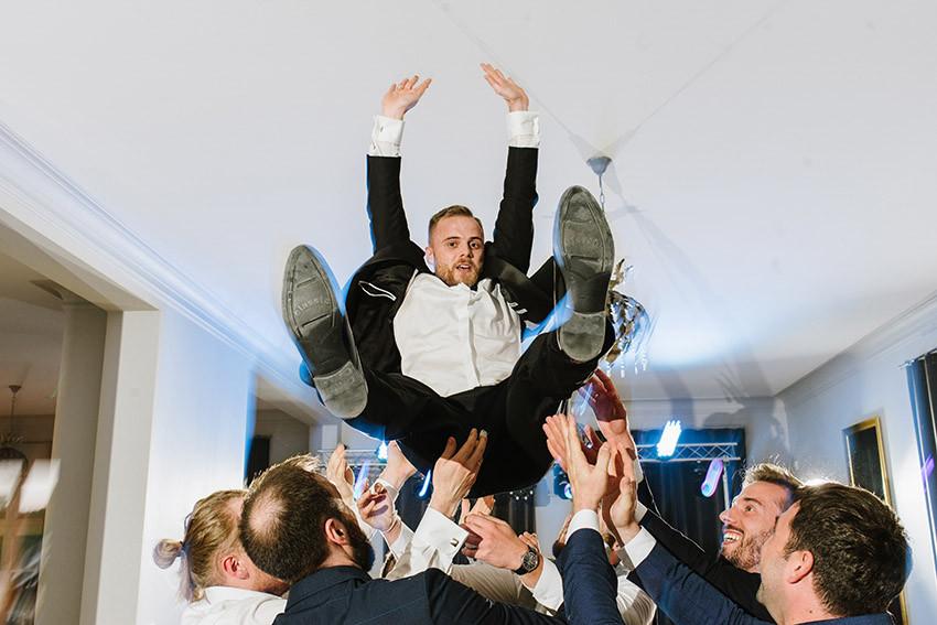 Pan Młody podrzucany na weselu przez gości