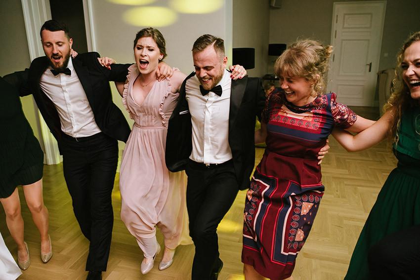 Pan Młody tańczy z gośćmi na weselu