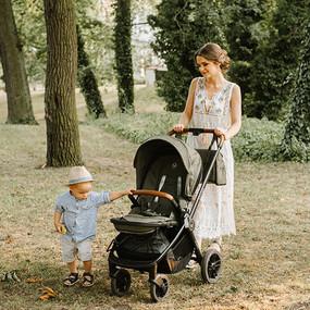 mama z wózkiem i synek spacerują w parku podczas rodzinnej sesji zdjęciowej