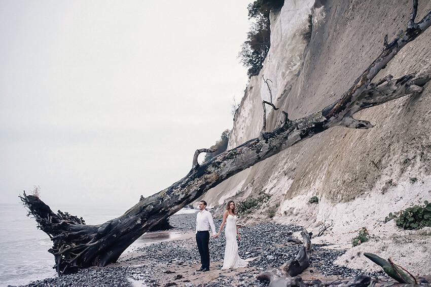 powalone drzewo i para młoda na plaży w Rugii