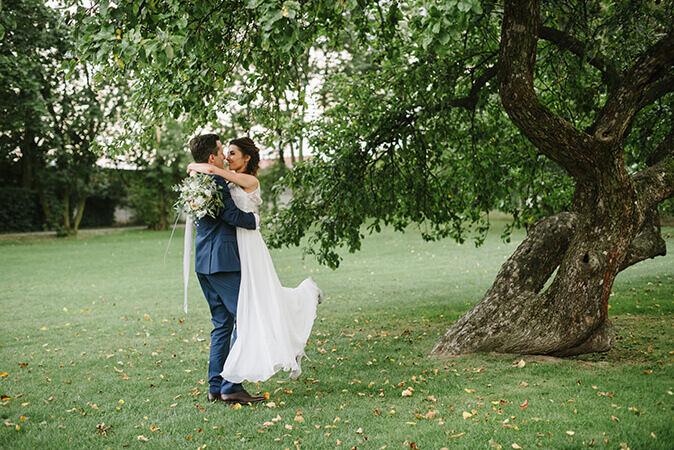 panna młoda w sukience od Ochocka Atelier przytula się z mężem w ogrodzie Bagatelki