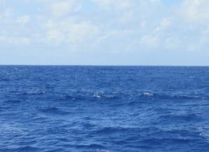 Foto do mar aberto com algumas ondas pequenas, com céu azul e algumas nuvens brancas.