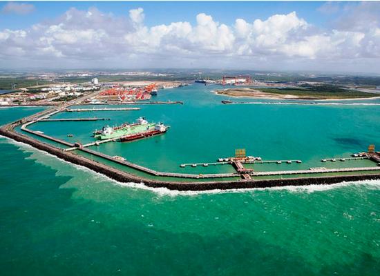 Foto vista de cima mostrando um porto. A água está com coloração verde azulada.