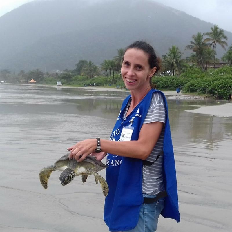 Foto de uma pessoa com o colete azul do Projeto TAMAR, carregando uma tartaruga. No fundo da imagem temos a praia e alguns coqueiros e outros tipos de vegetação.
