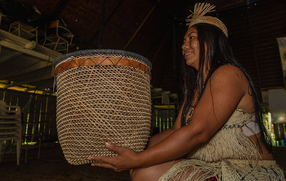 Indigenous woman from the Huitoto tribe standing with handmade baskets.jpg