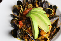 plate of mussels with pasta and avocade