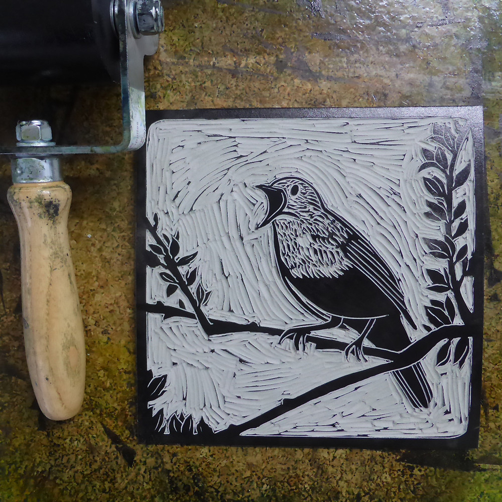 Inking the linocut block for the Sutton Hoo nightingale bird illustration.