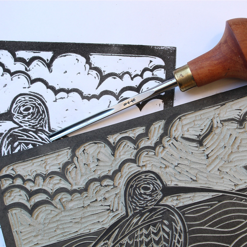 Test printing the Sutton Hoo curlew and Anglo-Saxon boat linocut illustration