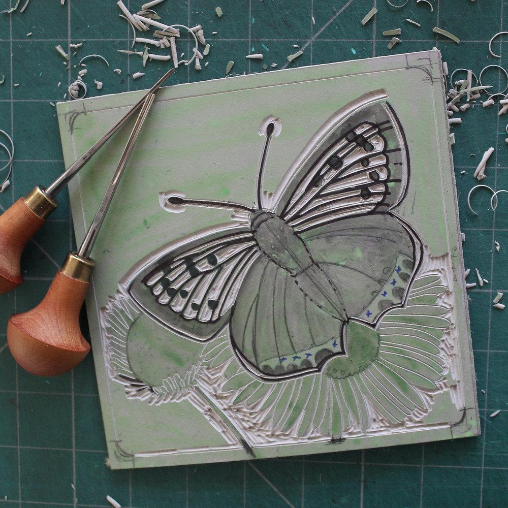 Carving the copper butterfly into the lino block.