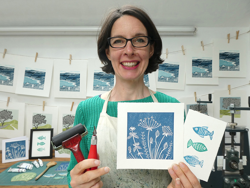 In my studio holding examples of linocut prints you can create on the course