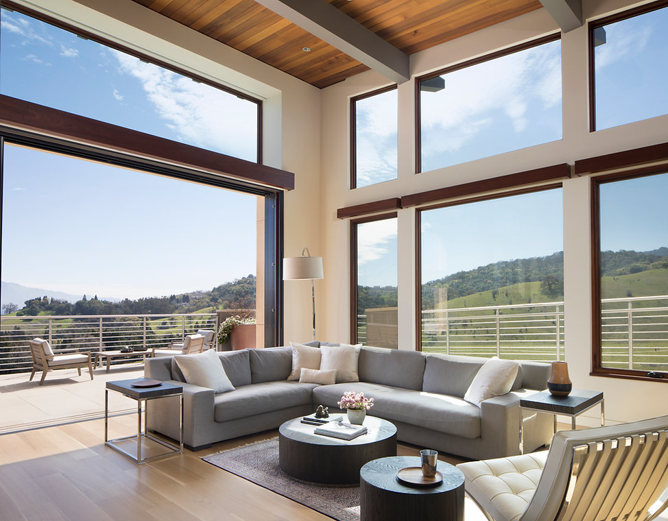 New home build livingroom with large windows and doors leading to outside patio with a view.