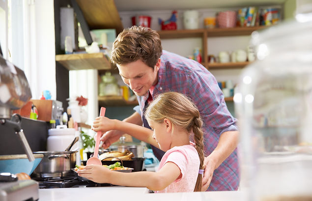 daughter-helping-father-to-cook-meal-in-