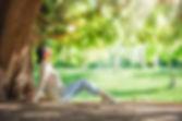woman-relaxing-under-big-tree-PVAR58H.jp