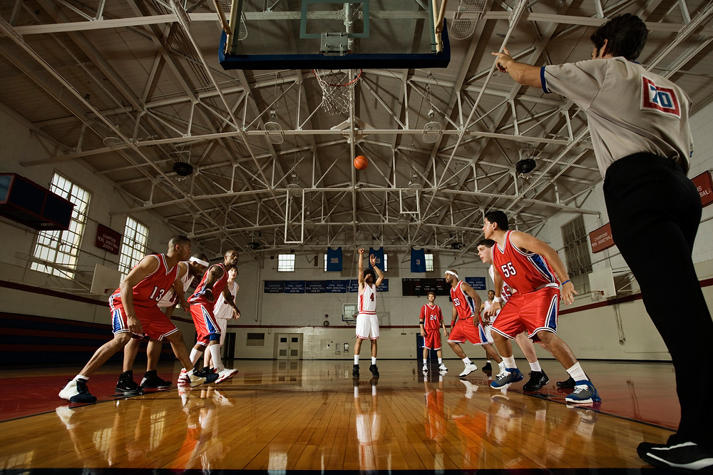 A basketball player throws a basketball at the hoop during a basketball match. Other players watch on. This takes place in a gym hall.