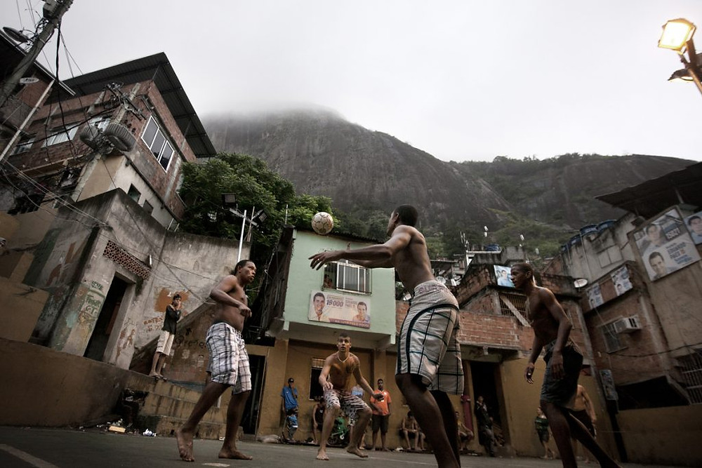 Several teenagers play soccer in Rocinha, the biggest shantytown of Rio de Janeiro, Brazil, November 26, 2012. Initiated in 2008, the UPP, short for Unidade de Polícia Pacificadora (in English, Pacifier Police Unit or Police Pacification Unit), is a new system of community policing in Rio de Janeiro's favelas once run by drug traffickers. While many believe that UPPs have helped quell violence by opening the doors of the favelas to public services such as legal electricity supply, garbage collection, education, public works and social assistance program, others see the pacification program as a temporary cover-up to security problems in Rio de Janeiro.