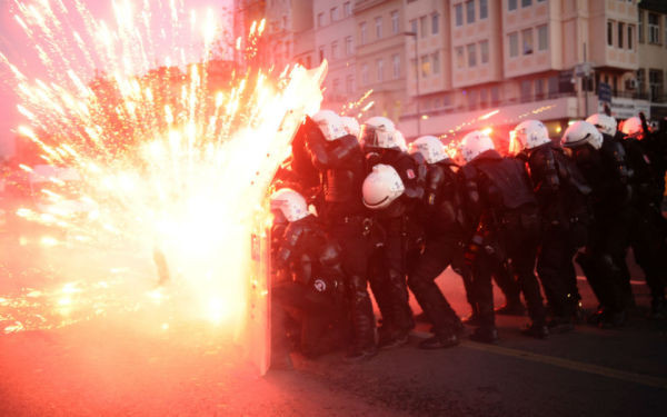 Turkish riot police officers take cover as Kurdish protesters shoot fireworks at them during clashes in central Istanbul on Dec. 7, 2013.  BULENT KILIC/AFP/Getty Images
