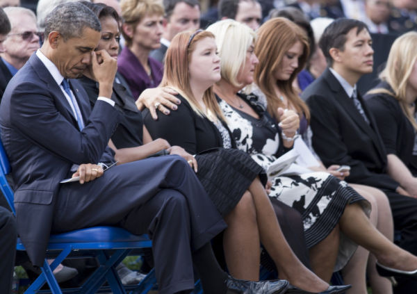 US President Barack Obama listens during a memorial service at the Marine Barracks September 22, 2013 in Washington, DC, for victims of the September 16, 2013 shooting at the Washington Navy Yard that took 12 lives.  (Photo credit BRENDAN SMIALOWSKI/AFP/Getty Images)