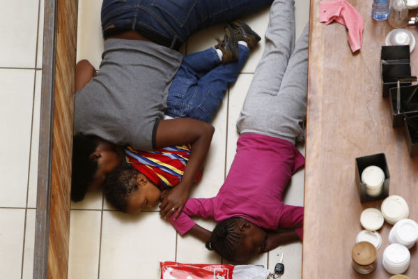 A mother and her children hide from gunmen at Westgate Shopping Centre in Nairobi September 21, 2013.    REUTERS/Siegfried Modola