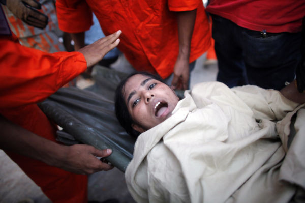 A garment worker reacts after being rescued by workers after the Rana Plaza building collapsed, in Savar, 30 km (19 miles) outside Dhaka April 24, 2013.  REUTERS/Andrew Biraj