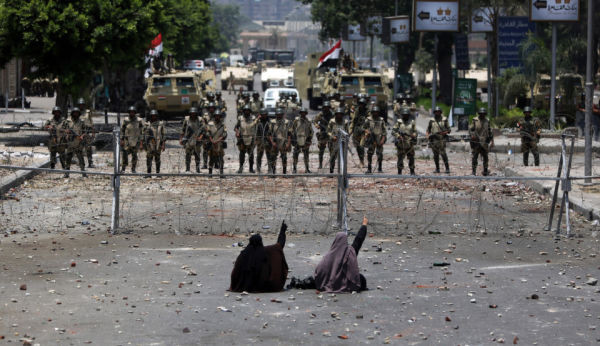 Two veiled Egyptian women, supporters of deposed president Mohamed Morsi, sit in front police standing behind barbed wire fencing that blocks the access to the headquarters of the Republican Guard in Cairo on July 8, 2013.  (Photo credit MAHMUD HAMS/AFP/Getty Images)