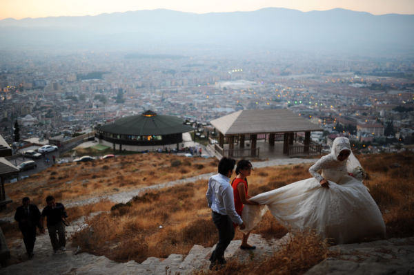 A newly married couple walks up a hill with a view of the city of Antakya, on August 29, 2013.  (AFP PHOTO / BULENT KILIC/AFP/Getty Images)