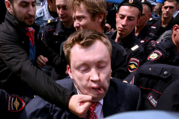 Unknown anti-gay activist hits Russia's gay and LGBT rights activist Nikolai Alexeyev (C) during unauthorized gay rights activists rally in cental Moscow on May 25, 2013.   (Photo credit ANDREY SVITAILO/AFP/Getty Images)