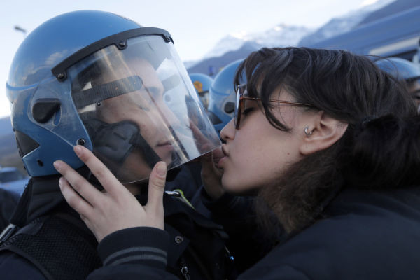 A demonstrator kisses a riot police officer on November 16, 2013 during a protest in Susa against the high-speed train (TAV in Italian) line between Lyon and Turin. (Photo credit should read MARCO BERTORELLO/AFP/Getty Images)