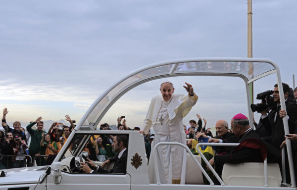 Pope Francis waves at faithfuls standing along the beachfront in Rio de Janeiro as hundreds of thousands of Catholic pilgrims attending World Youth Day (WYD) wait for him at Copacabana beach for the final mass on July 28, 2013.  (Photo credit EVARISTO SA/AFP/Getty Images)