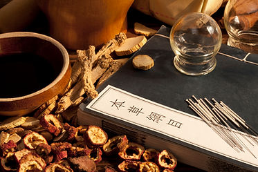 Table decorated with Chinese herbs, acupuncture needles and a Chinese medicine textbook